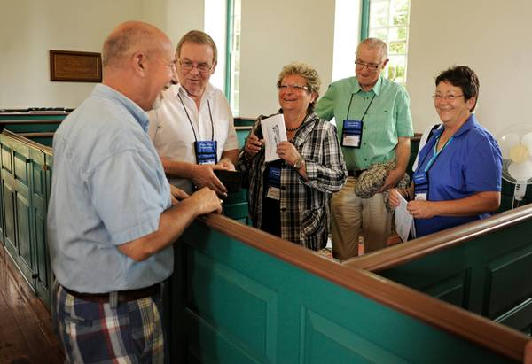 Little Fork Church member Rick Furnival (left) chats with a group of Germanna descdendents. (Peter Cihelka/Free-Lance Star)
